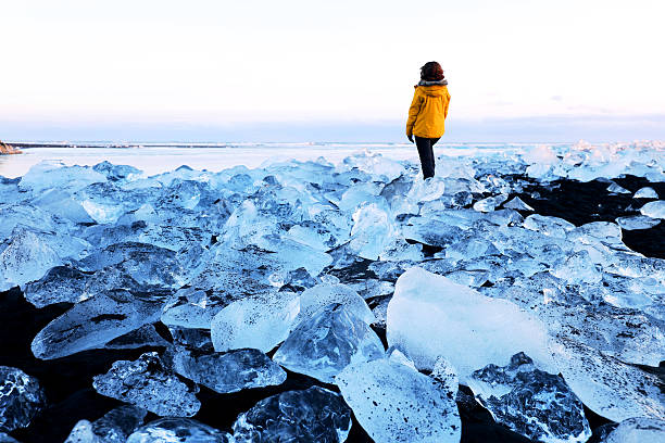 Traveller in Surreal Ice Landscape on Jokulsarlon Coast in Iceland A female traveller is standing in the surreal ice landscape on the beach near Jokulsarlon glacial lagoon in Iceland. Many big pieces of ice are washed ashore. The icebergs are coming from a melting Vatnajokull Glacier and are scattered all along the coast. This image is taken on a cold winter evening. jokulsarlon stock pictures, royalty-free photos & images