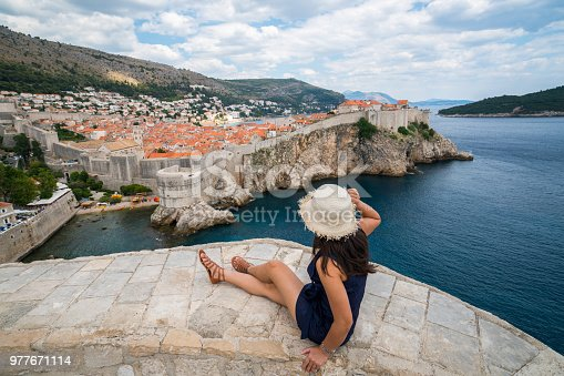 Traveller looking at view of Dubrovnik Old Town, in Dalmatia, Croatia, the prominent travel destination of Croatia. Dubrovnik old town was listed as UNESCO World Heritage Sites in 1979.