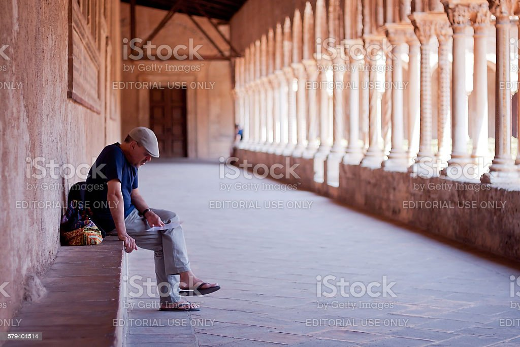Traveller resting in Monreale Cloister, Sicily, Italy stock photo