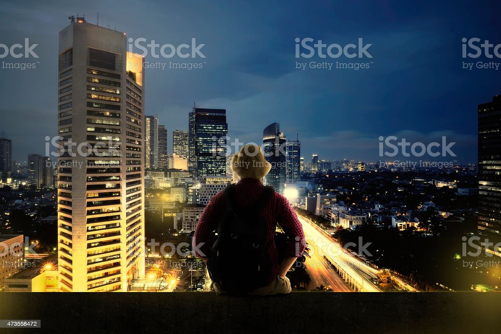 Traveller Sitting On The Top Of Building stock photo