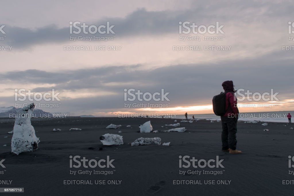 Traveller standing at diamond beach in Jokulsarlon ,famous place in South Iceland stock photo