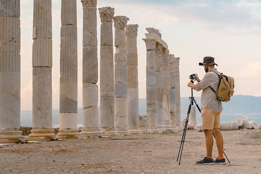 Traveller tourist photographer is taking photo with tripod in ancient ruins of Laodicea on the Lycus , Pamukkale