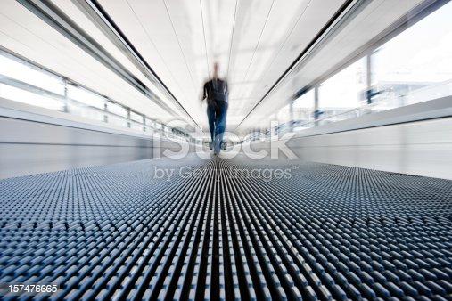 istock Traveller walking on moving stairway airport walkway 157476665