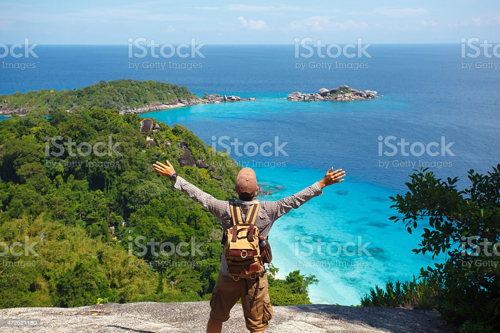 traveller with backpack standing on the rocks royalty-free stock photo