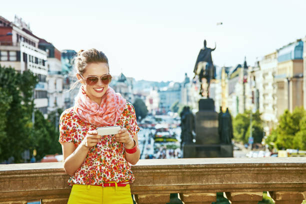 traveller woman on Vaclavske namesti in Prague writing sms The spirit of old Europe in Prague. happy modern traveller woman on Vaclavske namesti in Prague, Czech Republic writing sms wenceslas square stock pictures, royalty-free photos & images