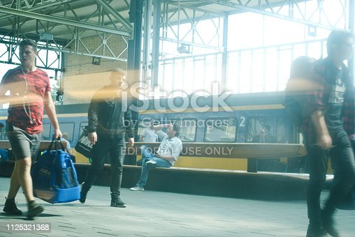 istock Travellers and commuters ready to board a (Nederlandse Spoorwegen) NS train at Eindhoven railway station, the Netherlands 1125321368