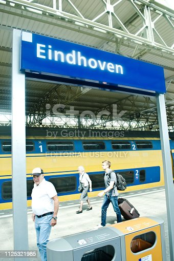 istock Travellers and commuters ready to board a (Nederlandse Spoorwegen) NS train at Eindhoven railway station, the Netherlands 1125321985