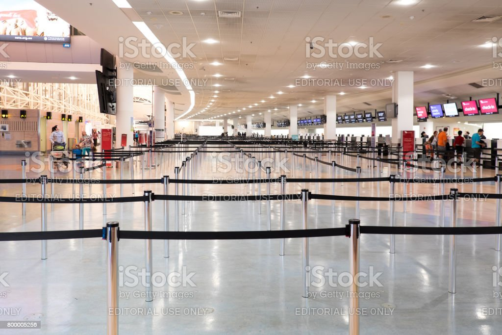 Travellers at the check-in area at Auckland International Airport early in the morning stock photo