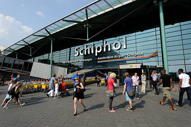 travellers at the entrance of amsterdam airport schiphol - schiphol stockfoto's en -beelden