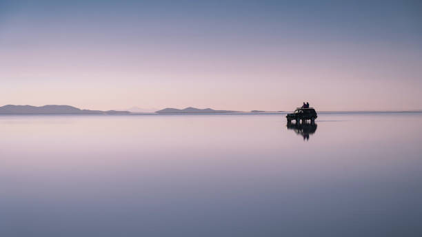 Travellers Exploring Uyuni Salt Flats at Sunrise in Bolivia, South America stock photo
