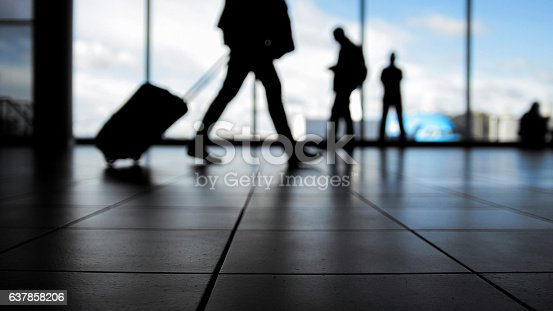 istock Travellers in airport walking to departures by escalator in front 637858206