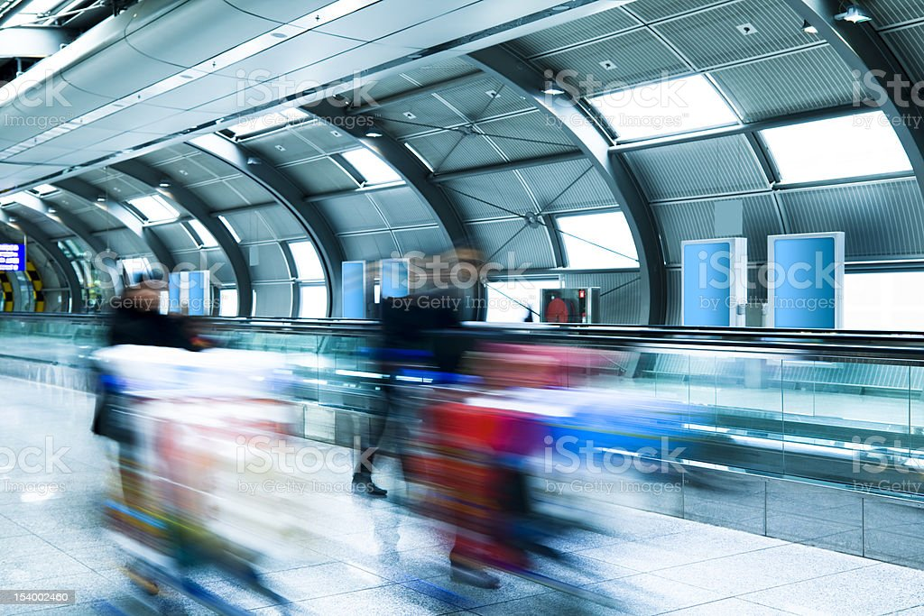 Travellers Pushing Luggage on Trolleys Through Airport Tunnel royalty-free stock photo