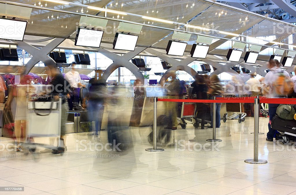 Travellers queing to check-in at an International Airport. stock photo