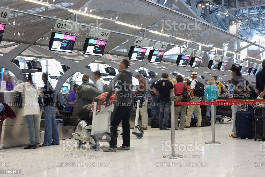 Travellers queing to check-in at an International Airport. royalty-free stock photo