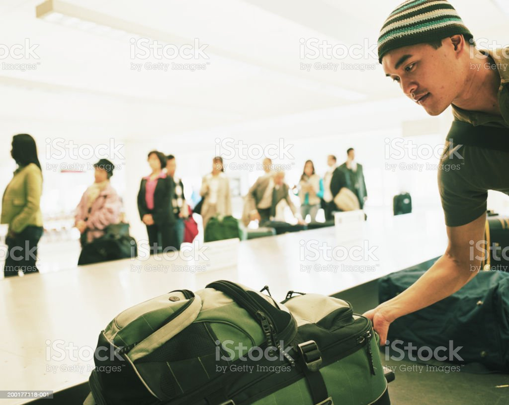 Travellers standing by airport carousel, young man picking luggage stock photo
