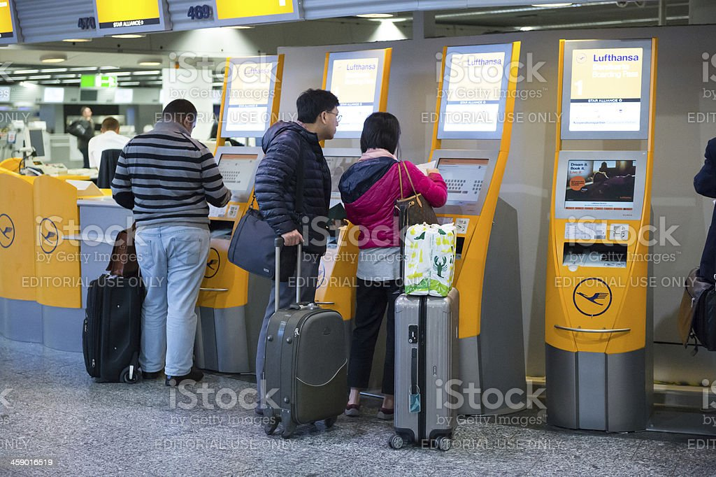 Travellers using Lufthansa self check-in machines at Frankfurt Airport stock photo
