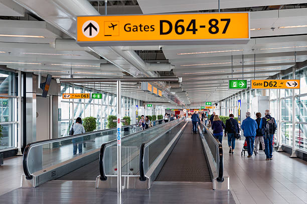 travellers walking to the gate at schiphol airport, the netherlands - airport terminal stock photos and pictures