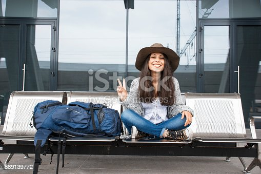 Young woman sitting on bench in station and waiting