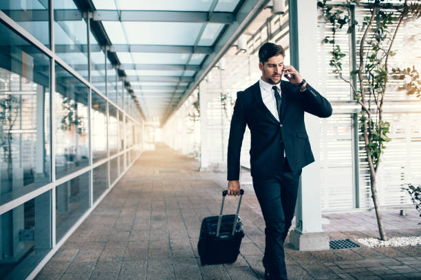 Travelling businessman making phone call stock photo