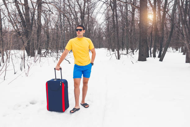 Travelling from winter to summer. Young cute guy in sunglasses, flip-flops, t-shirt and shorts with a tourist suitcase goes through the winter forest in the snow. Lets go to vacation. Creative idea. It's time for a vacation, went to warm countries in winter, a dream of rest. I want to go to the sea. shorts stock pictures, royalty-free photos & images