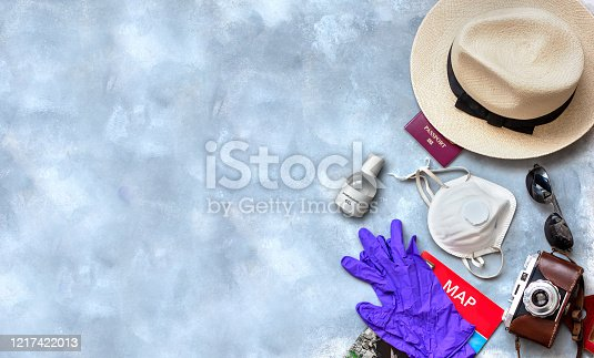 Hygienic mask and alcohol spray to protect against Coronavirus or COVID-19 and necessary traveler accessories on gray textured background