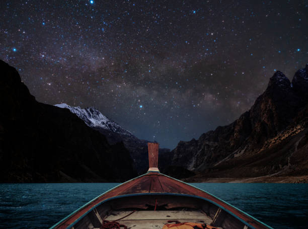 Travelling on lake at night by boat, sky full of star and milky way with mountains valley stock photo