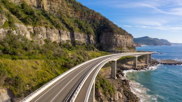 Travelling on the sea cliff bridge coastal drivel along the pacific ocean. Grand pacific drive, East coast of Australia. stock photo