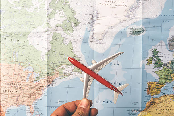 Travelling the world concept with a plain flying over map stock photo