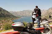 Rear view image of an embraced couple standing by the road with parked motorcycle aside admiring the view onto bay and coastal old town in summer