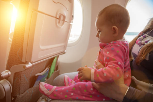 Travelling with infant. Mother and baby sitting together in airplane near the window in sunny day stock photo