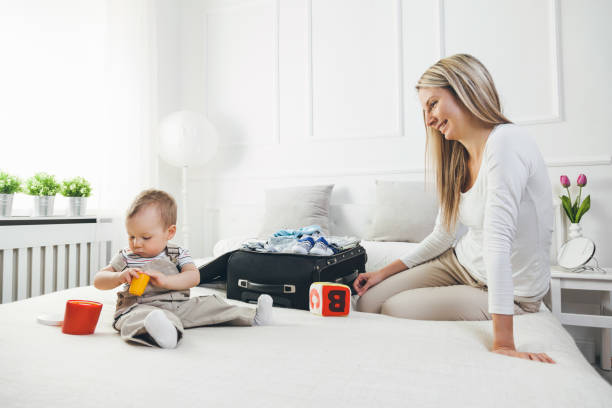 travelling with kids. happy mother with her child packing clothes for holiday - happy mom packing some toys stock photos and pictures