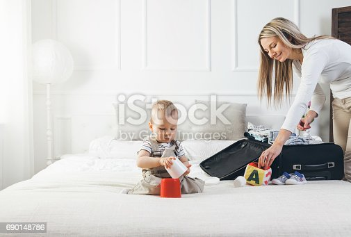 istock Travelling with kids. Happy mother with her child packing clothes for holiday 690148786