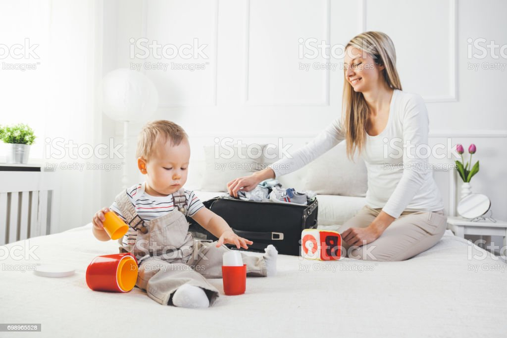 Travelling with kids. Happy mother with her child packing clothes for holiday stock photo