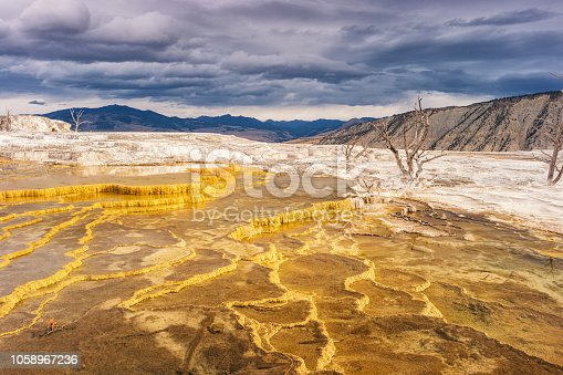 Stock photograph of the colorful travertine terraces at Mammoth Hot Springs in Yellowstone National Park on a cloudy day.