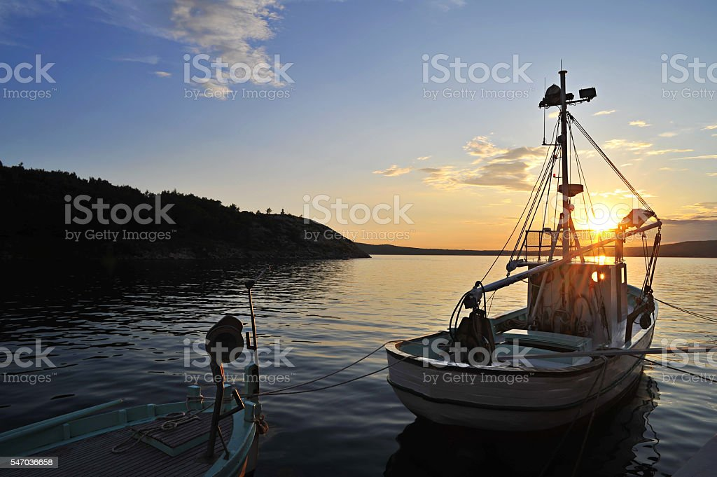 Trawler with dinghy at sunset near sea stock photo