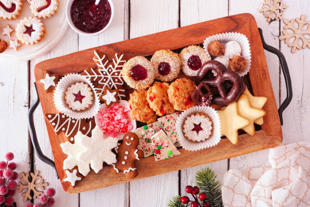 Tray of Christmas cookies and baking, top view table scene over white wood stock photo