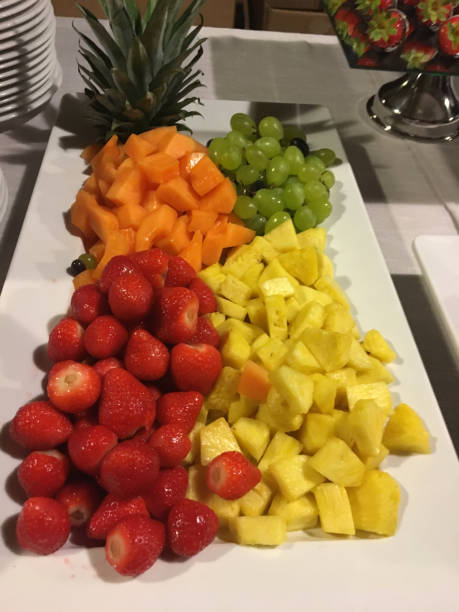 tray of fresh fruit with pineapple, strawberries, melon, grapes stock photo