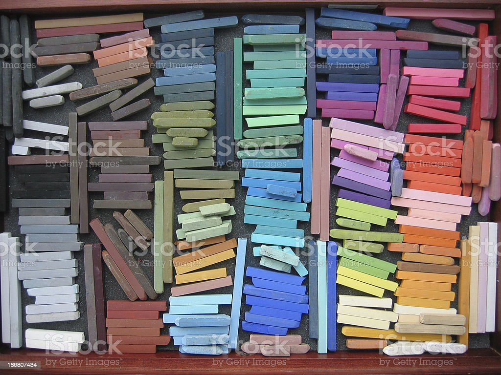 Wooden tray of whole and broken pastels. Colors arranged from...
