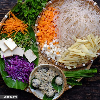 Top view tray of raw materials for vegan noodles soup with colorful vegetables as carrot, cabbage, bean sprouts, bamboo shoot, tofu, simple Vietnamese dish that healthy and nutrition
