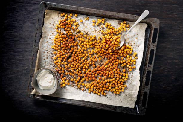 tray of roasted or baked seasoned chickpeas. - assado imagens e fotografias de stock