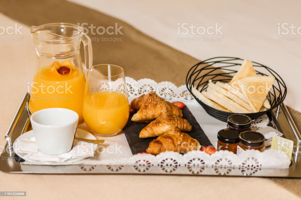 Metal tray with yummy breakfast pastry and fresh orange juice placed...