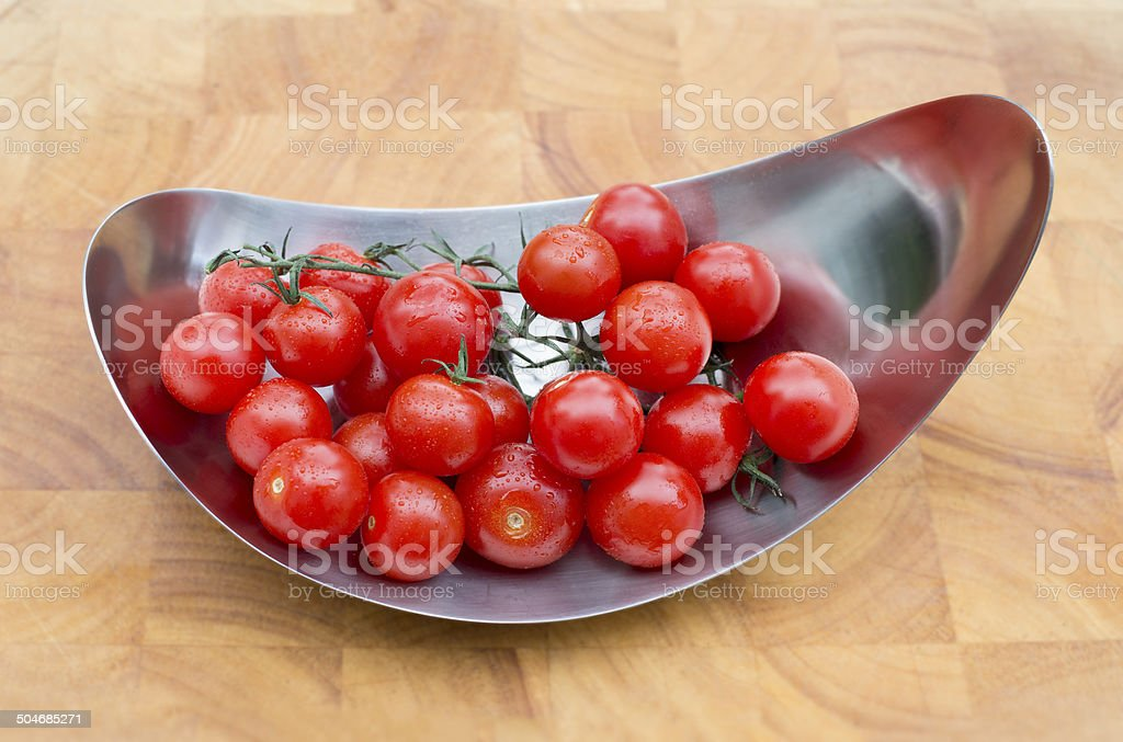 Tray with fresh red cherry tomatoes on wooden cutting board royalty-free stock photo
