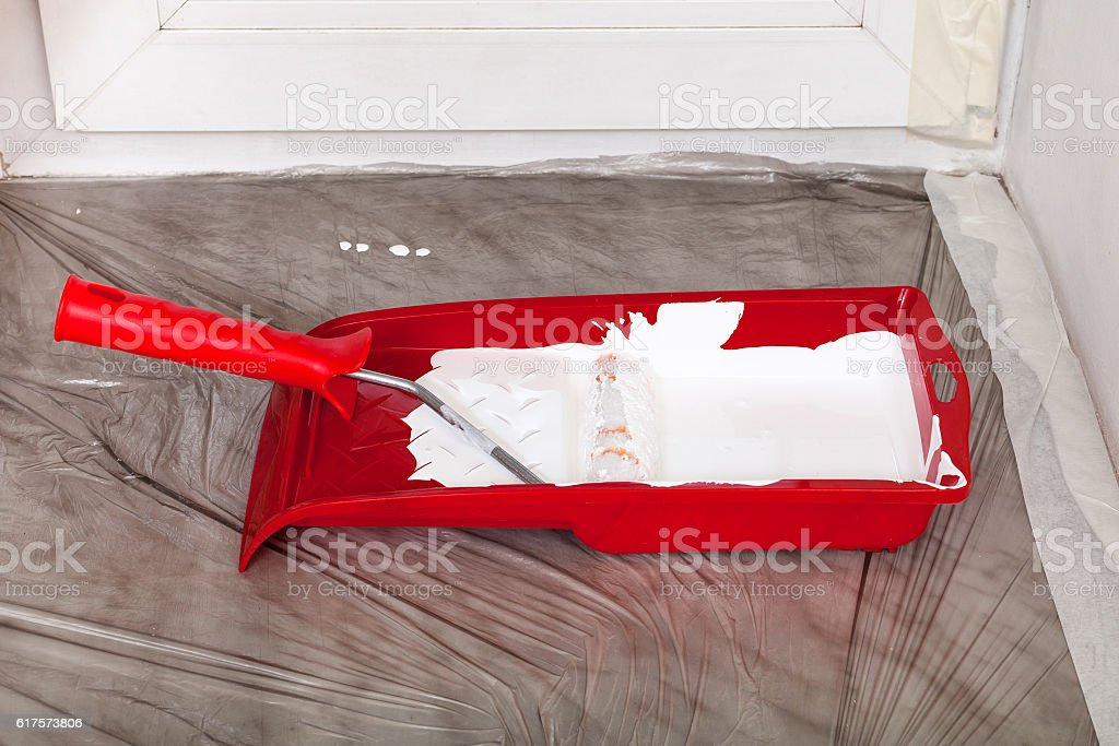 tray with white paint and roller on the windowsill stock photo