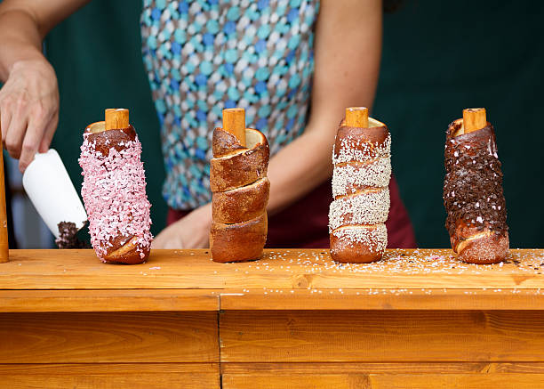 Trdelnik Czech traditional delicacy made from dough wrapped Trdelnik Czech traditional delicacy made from dough wrapped around a wooden or metal cylinder and roasted over an open fire. bohemia czech republic stock pictures, royalty-free photos & images
