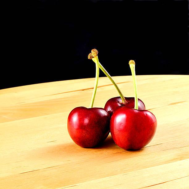 tre ciliegie rosse, formato quadrato tre ciliegie rosse su legno, con sfondo nero, formato quadrato quadrato stock pictures, royalty-free photos & images