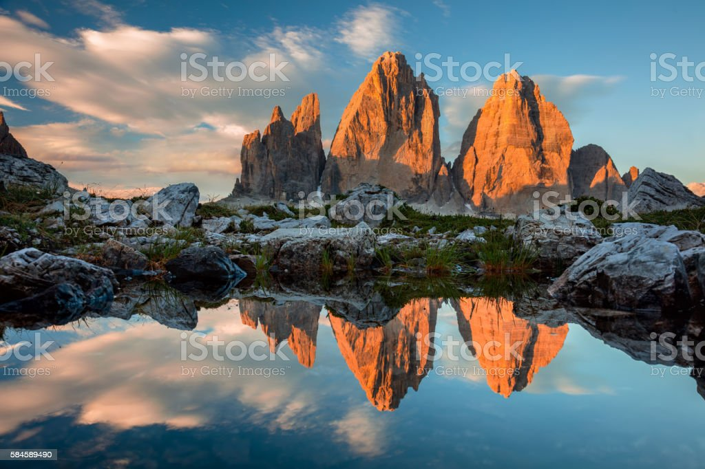 Tre Cime di Lavaredo with reflection in lake at sundown stock photo