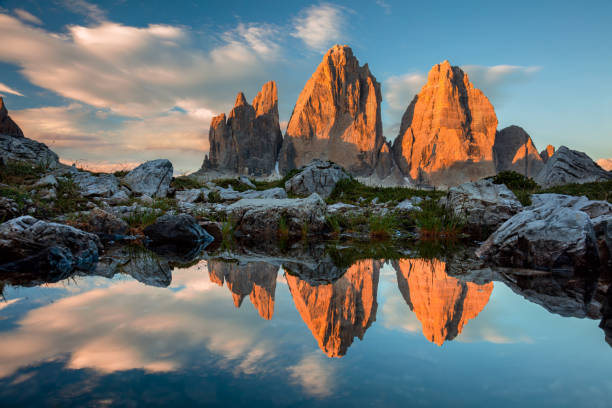 tre cime di lavaredo with reflection in lake at sundown - dolomiti foto e immagini stock