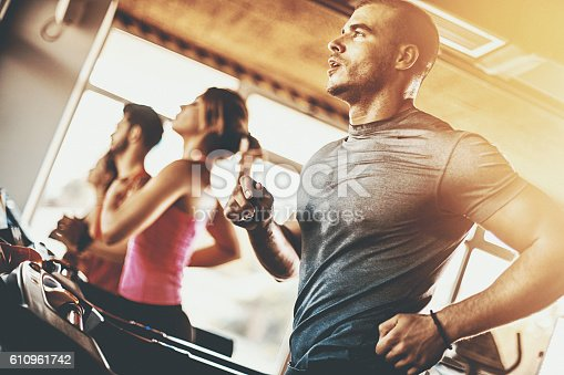 Closeup low angle view of a late 20'sman doing some cardio workout on a treadmill. He's wearing gray  sports t-shirt, soaked in sweat.There are three more people next to him, blurry. Back lit, Sun is flaring from the right hand side.