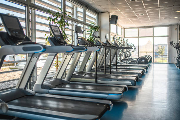 Treadmills and Cross Trainers Side by Side in Gym Long side view of treadmills and elliptical trainers side by side in modern gym illuminated by natural light. exercise machine stock pictures, royalty-free photos & images