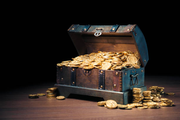 Treasure chest filled with gold coins Open treasure chest filled with gold coins / HIgh contrast image antiquities stock pictures, royalty-free photos & images